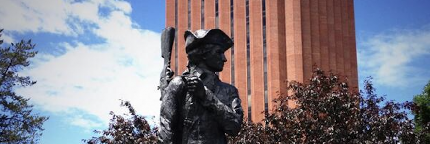 Statue of the UMass Minuteman with WEB DuBois Library in the background