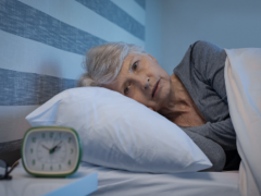 woman laying in bed next to alarm clock