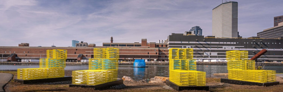 Photograph of FutureSHORELINE, a public art installation in Boston's Fort Point channel, featuring yellow and blue painted lobster traps stacked to indicate future flood levels.
