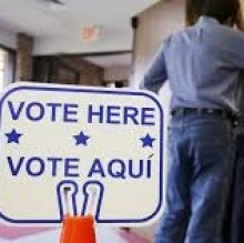 Voting day line, with sign reading Vote Here / vote aqui