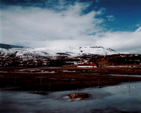 Photograph of snowy mountain and blue cloudy sky