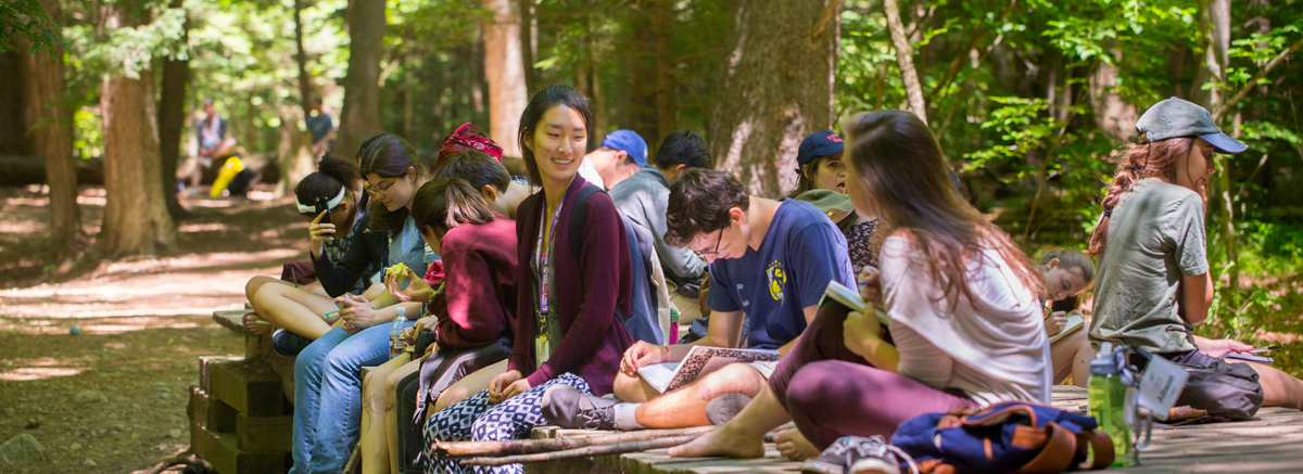 A group of students gather outdoors under trees.