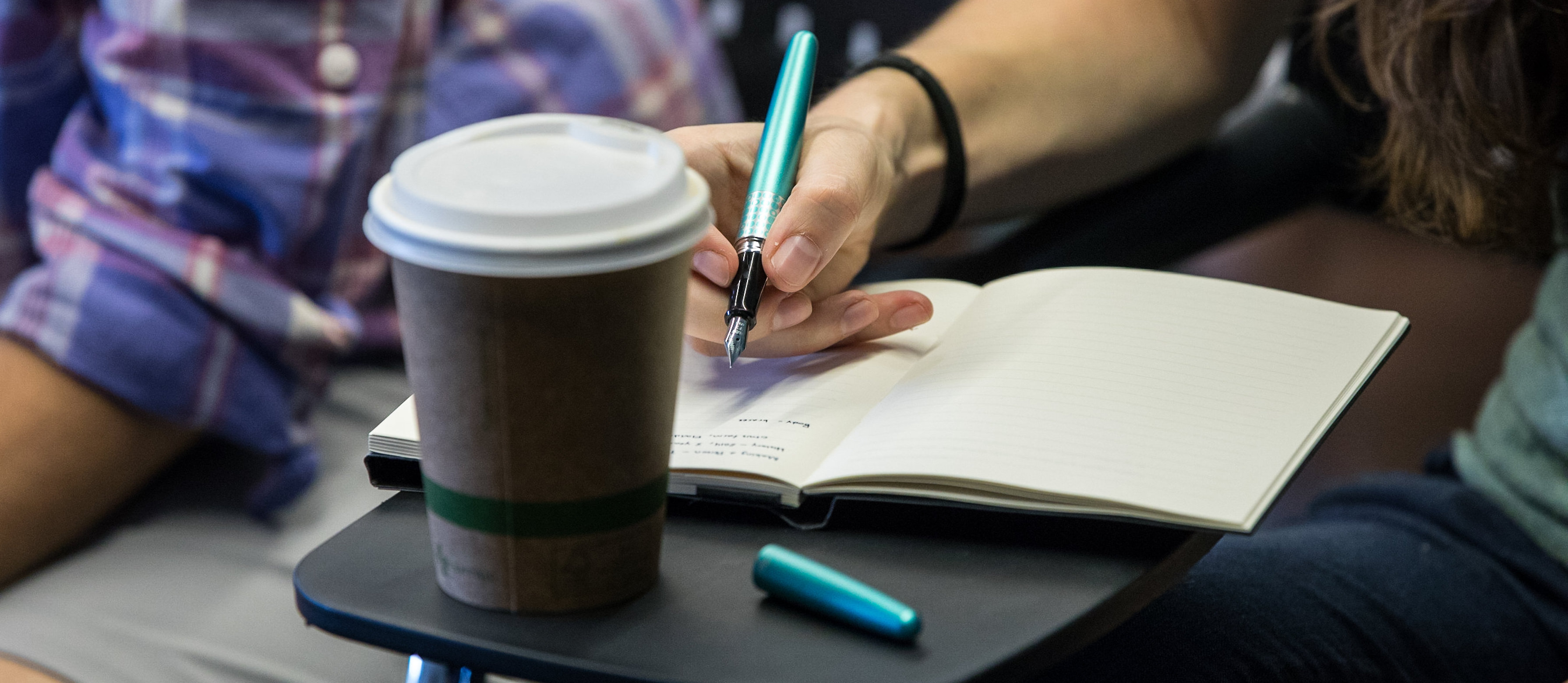 young writers writes at a desk with a coffee cup, pen and notebook
