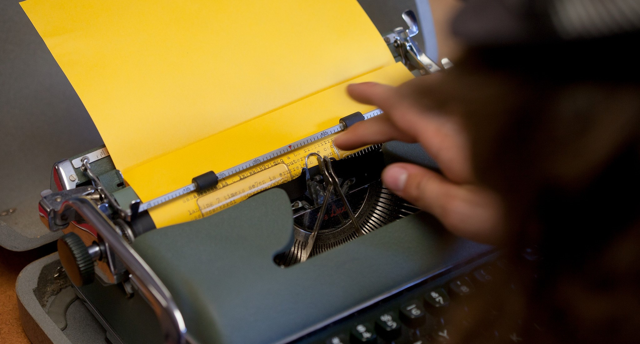 Student typing on a yellow page in a typewriter
