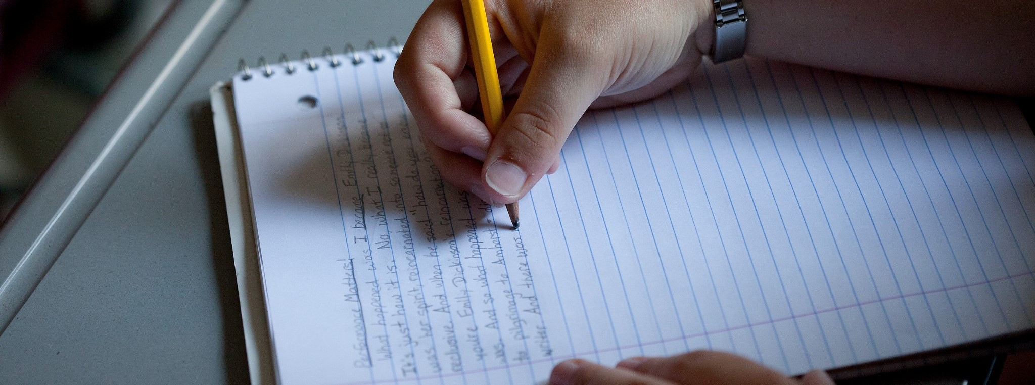 A young student's hand holding a pencil writing in a white notebook.