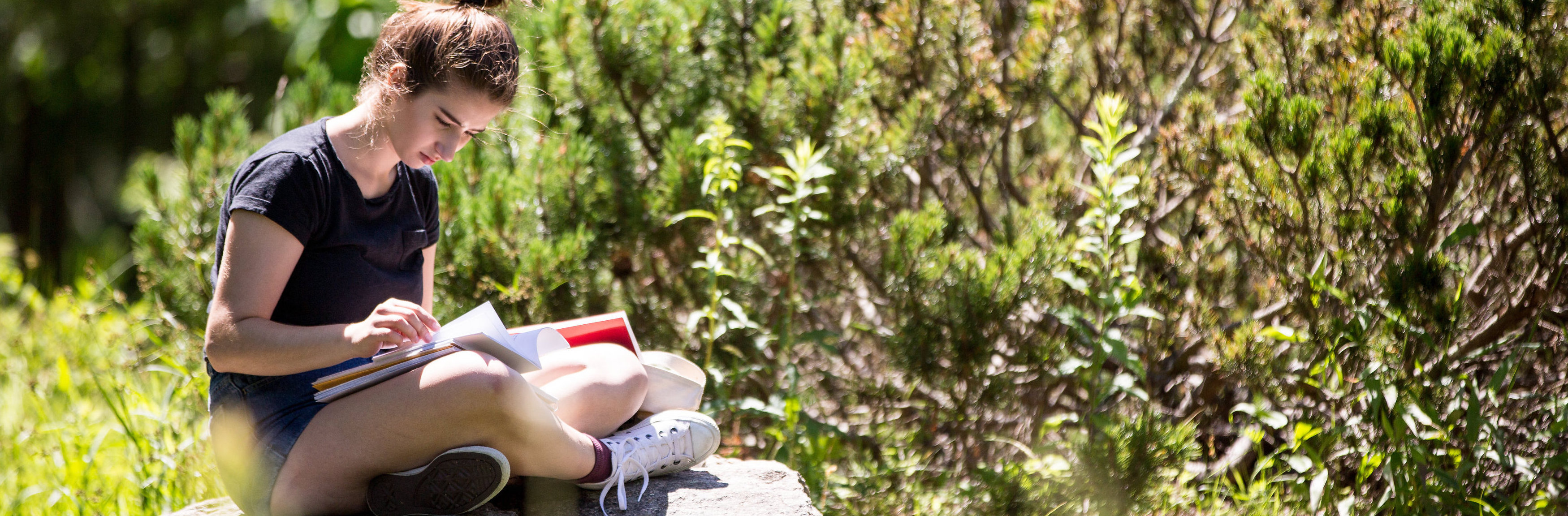 Young Writers sits outside writing in notebook