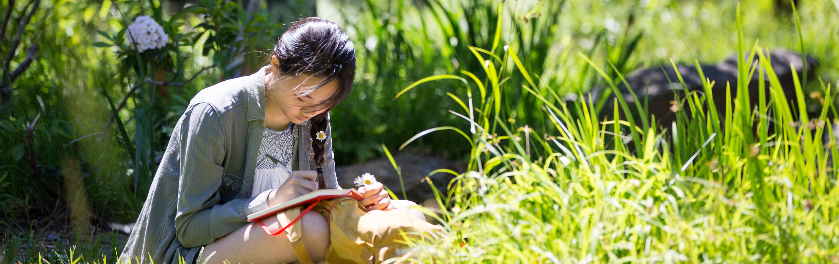 young writer writing in the grass