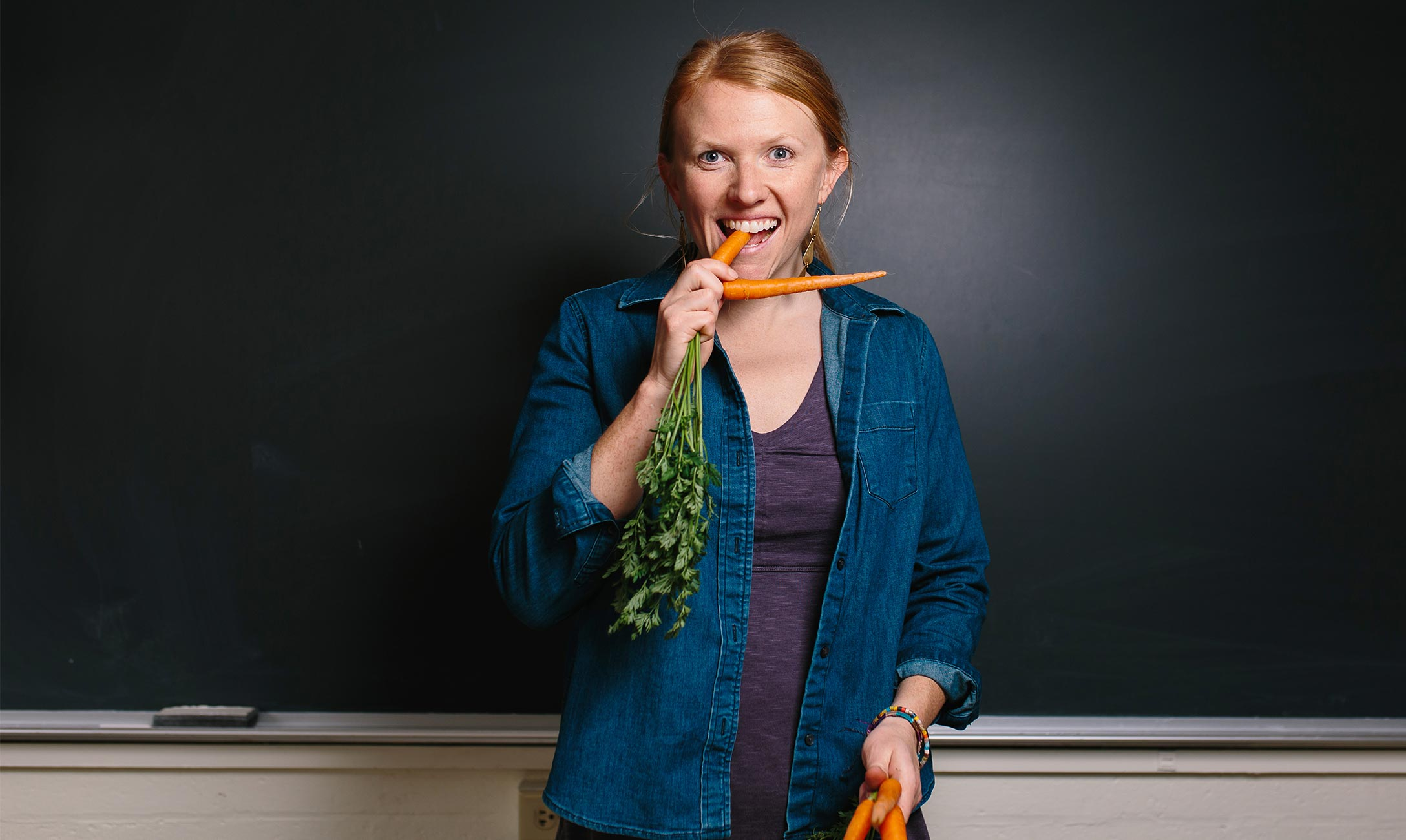 Person in blue jacket standing in classroom eating carrots.