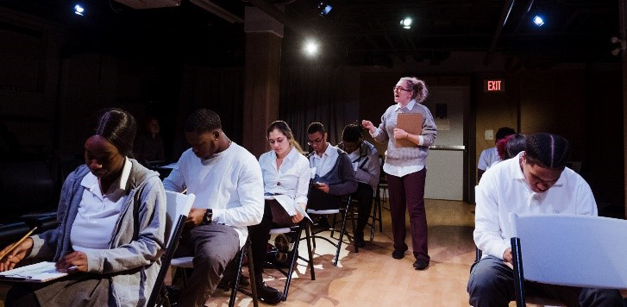Students are shown at desks taking a test while a proctor lectures, in a scene from The Wrong Answer Project.