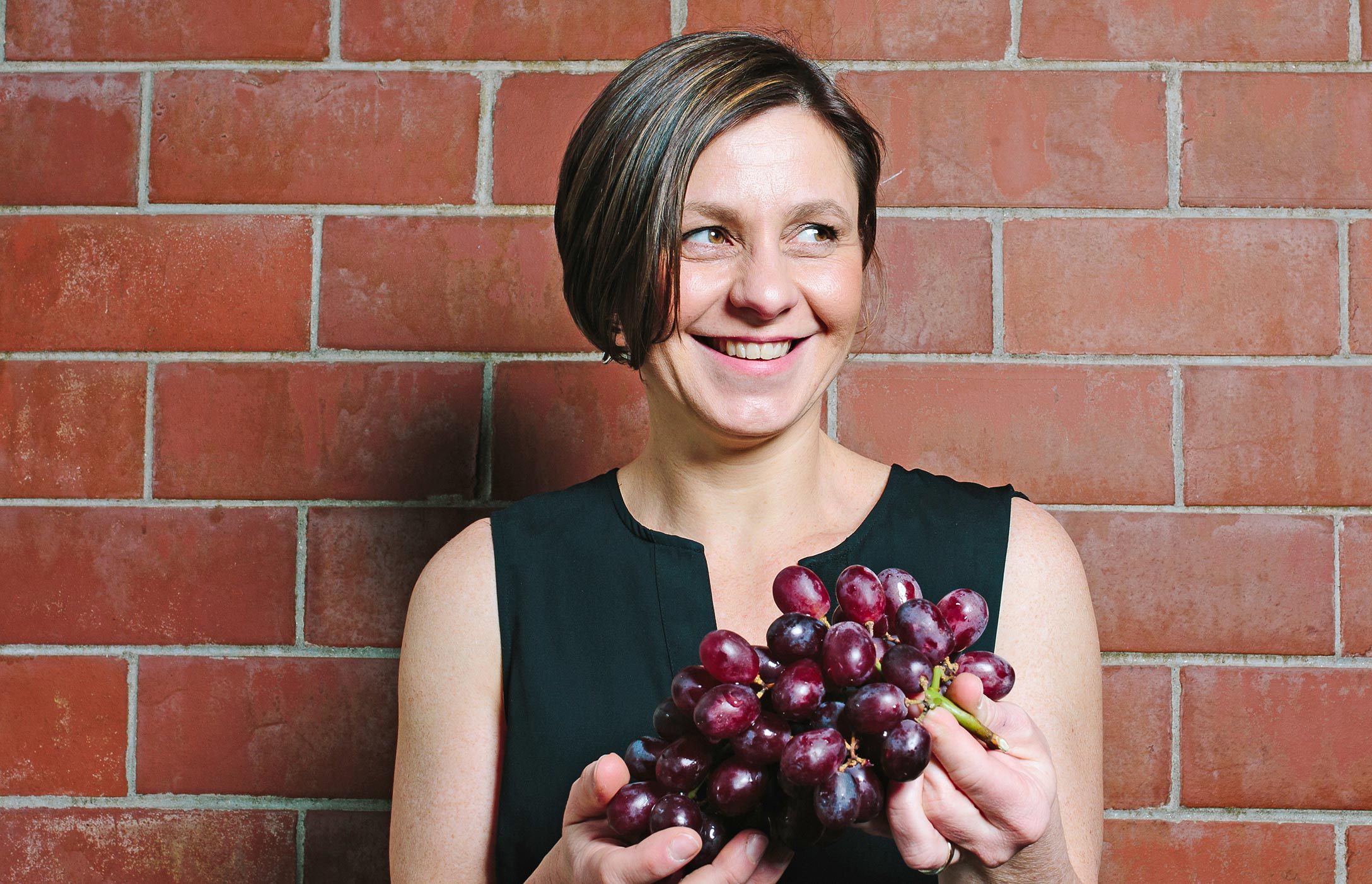 Elsa Petit stands against a brick wall, holding luscious purple grapes and looking away from the camera