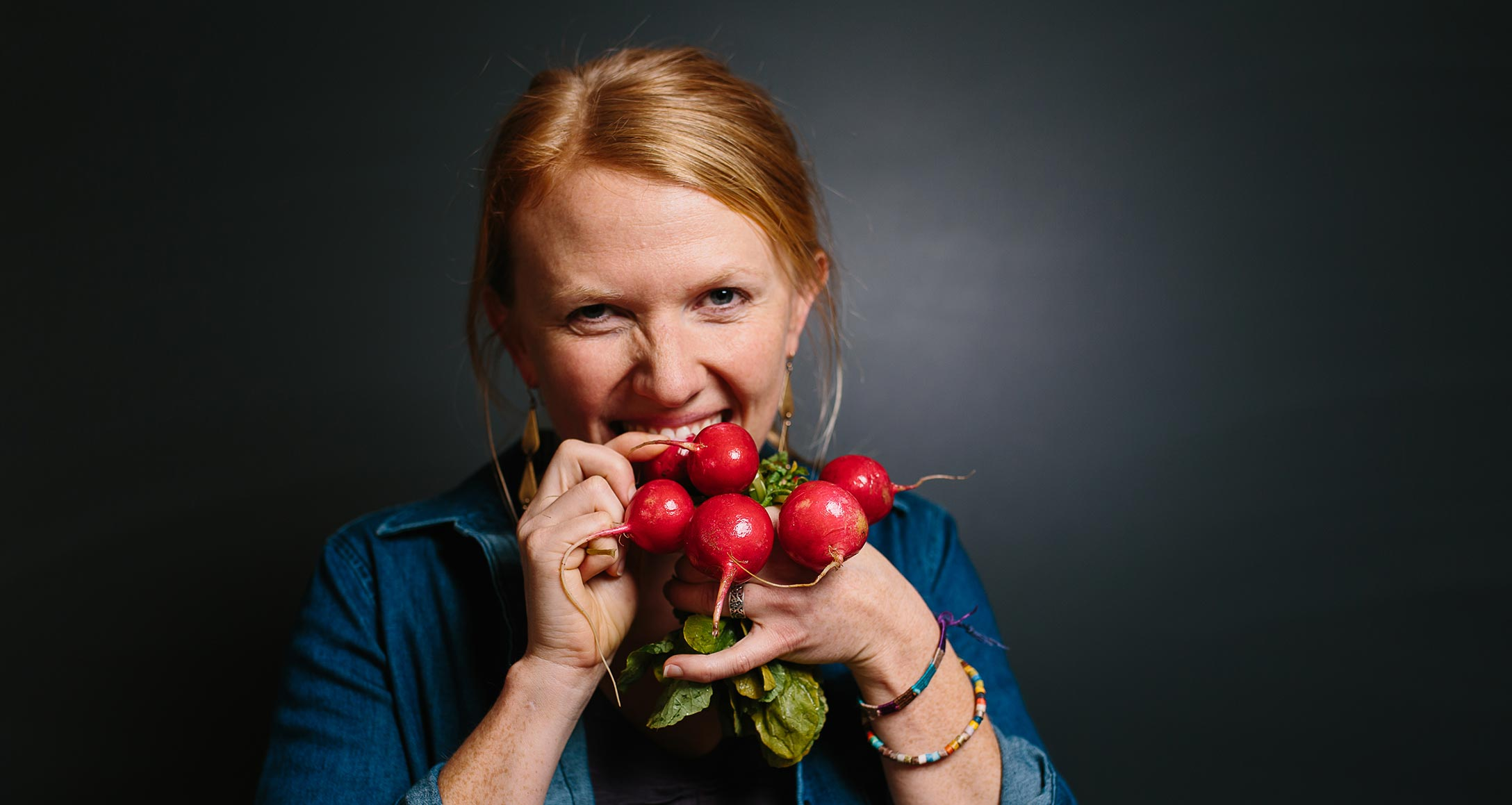 Sarah Berquist, program director for Sustainable Food and Farming, crunching fresh radishes