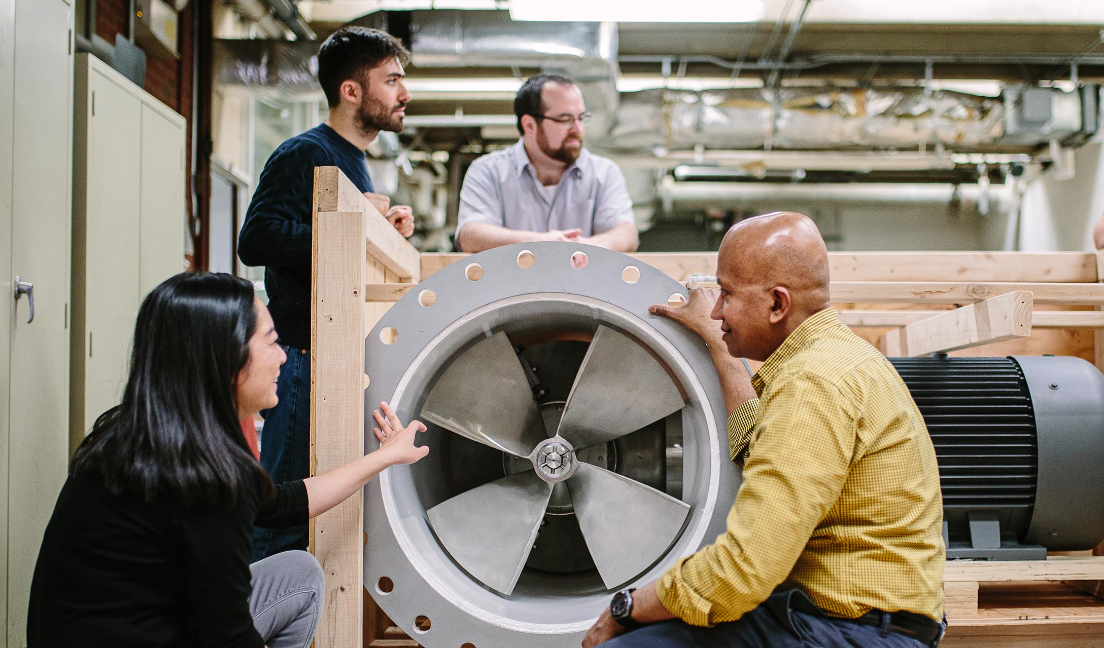 Krish Sharman and graduate students examine a newly-arrived water turbine for their lab
