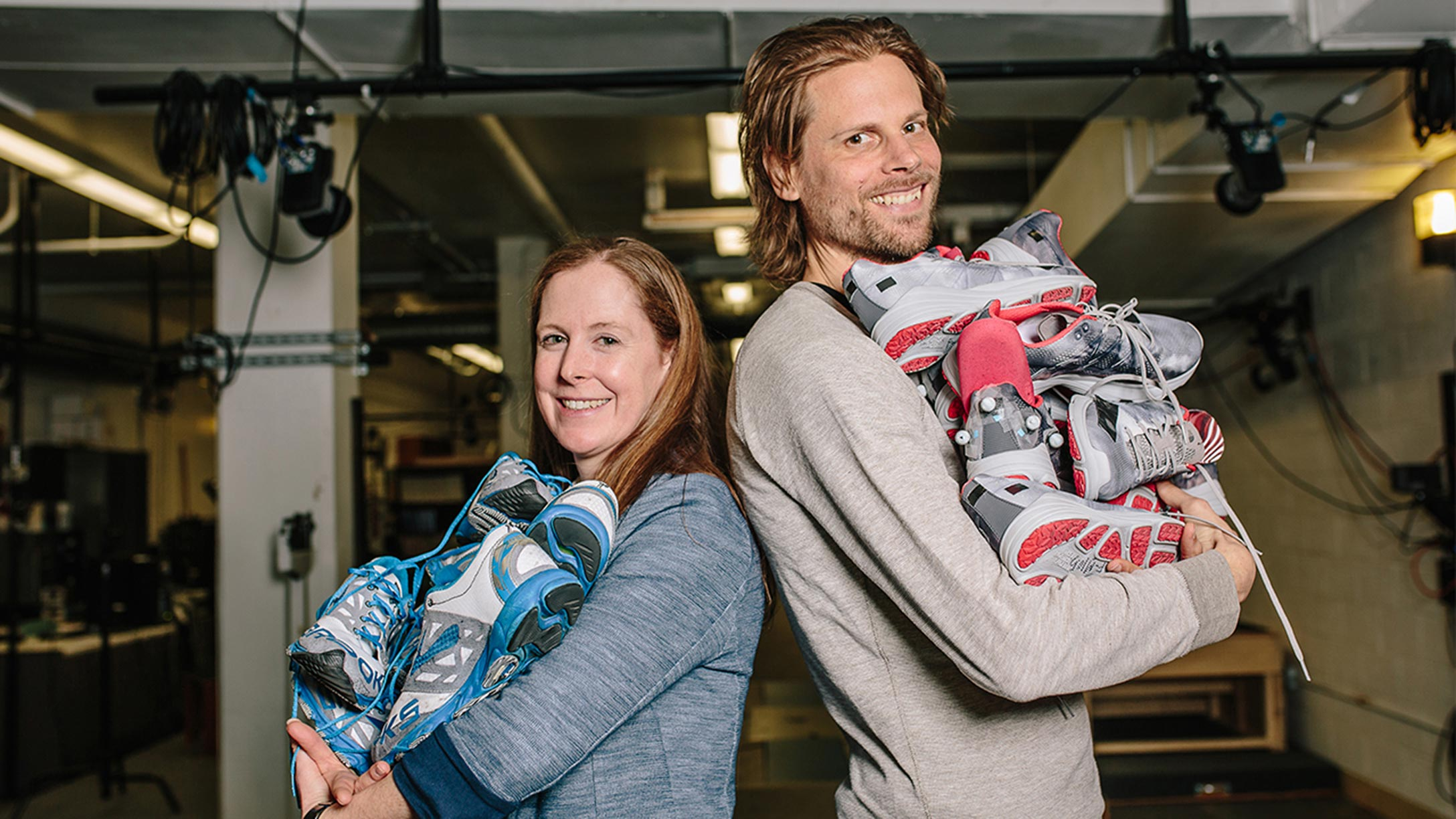 Professors Katherine Boyer and Wooter Hoogkamer of the Kinesiology lab stand back to back, each holding a large pile of athletic shoes from the testing lab.
