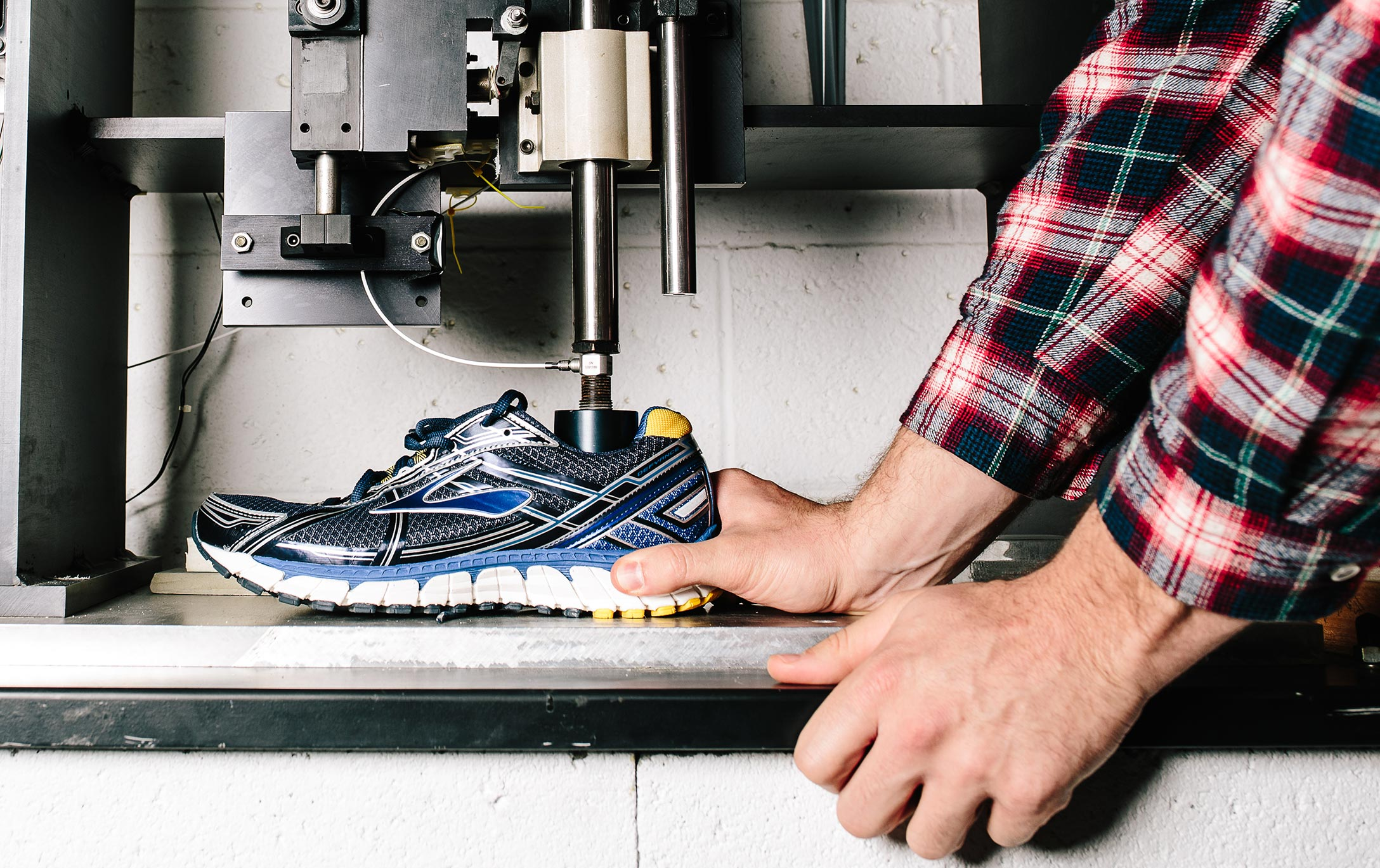 a hand holds an athletic shoe in a testing machine with metal hydraulic equipment placed inside the shoe opening