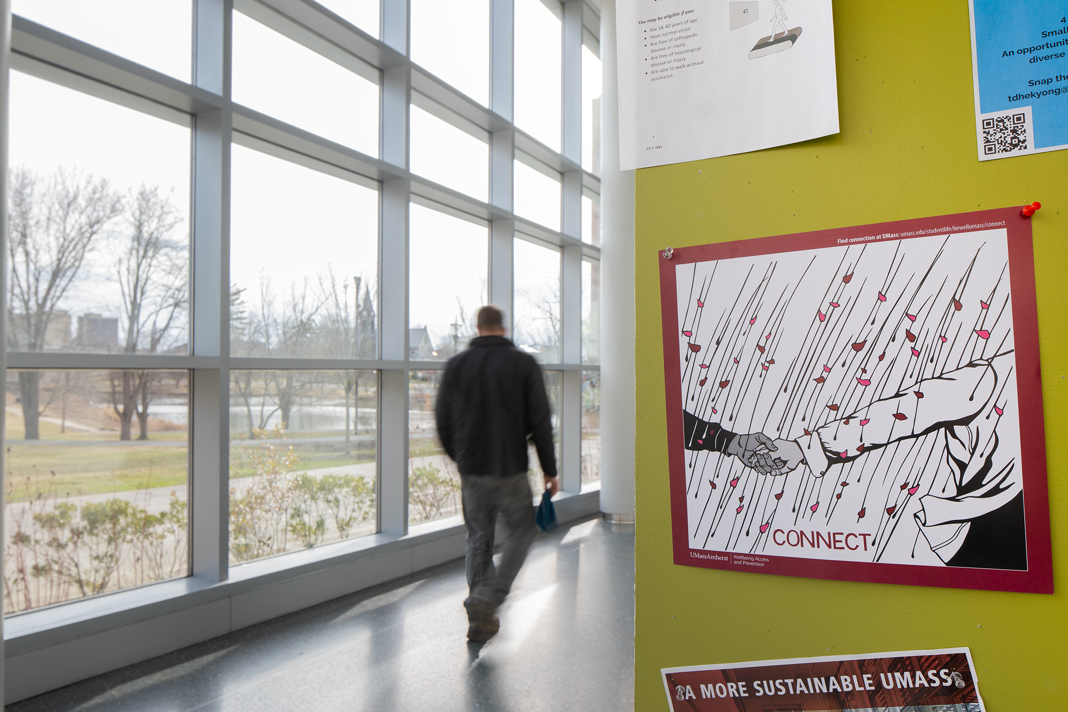 A poster reading Connect is shown on a wall in the Integrative Learning Center. Campus is seen through a nearby wall of windows. One blurred person walks away from the camera.