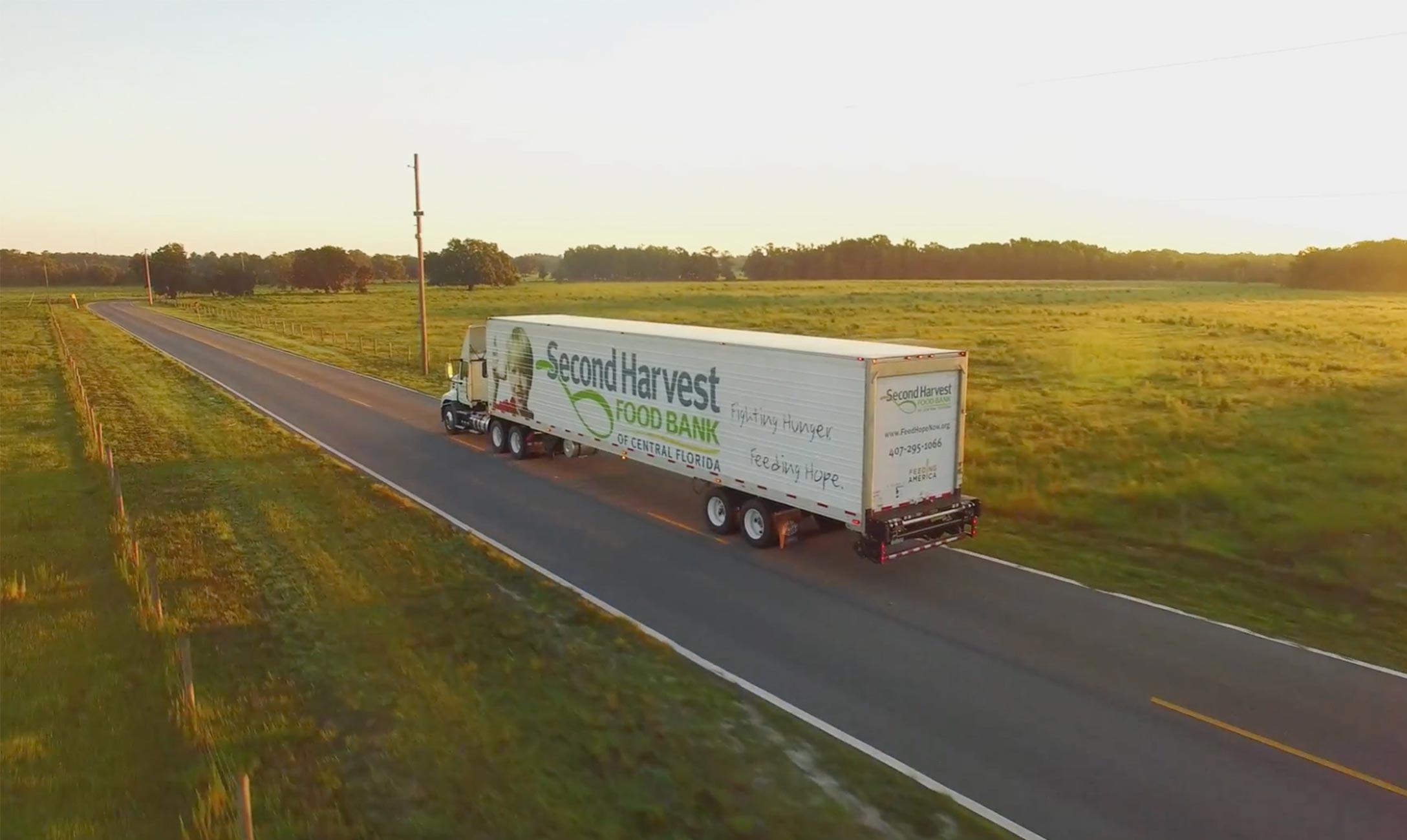 Second Harvest semi-truck driving on flat road.