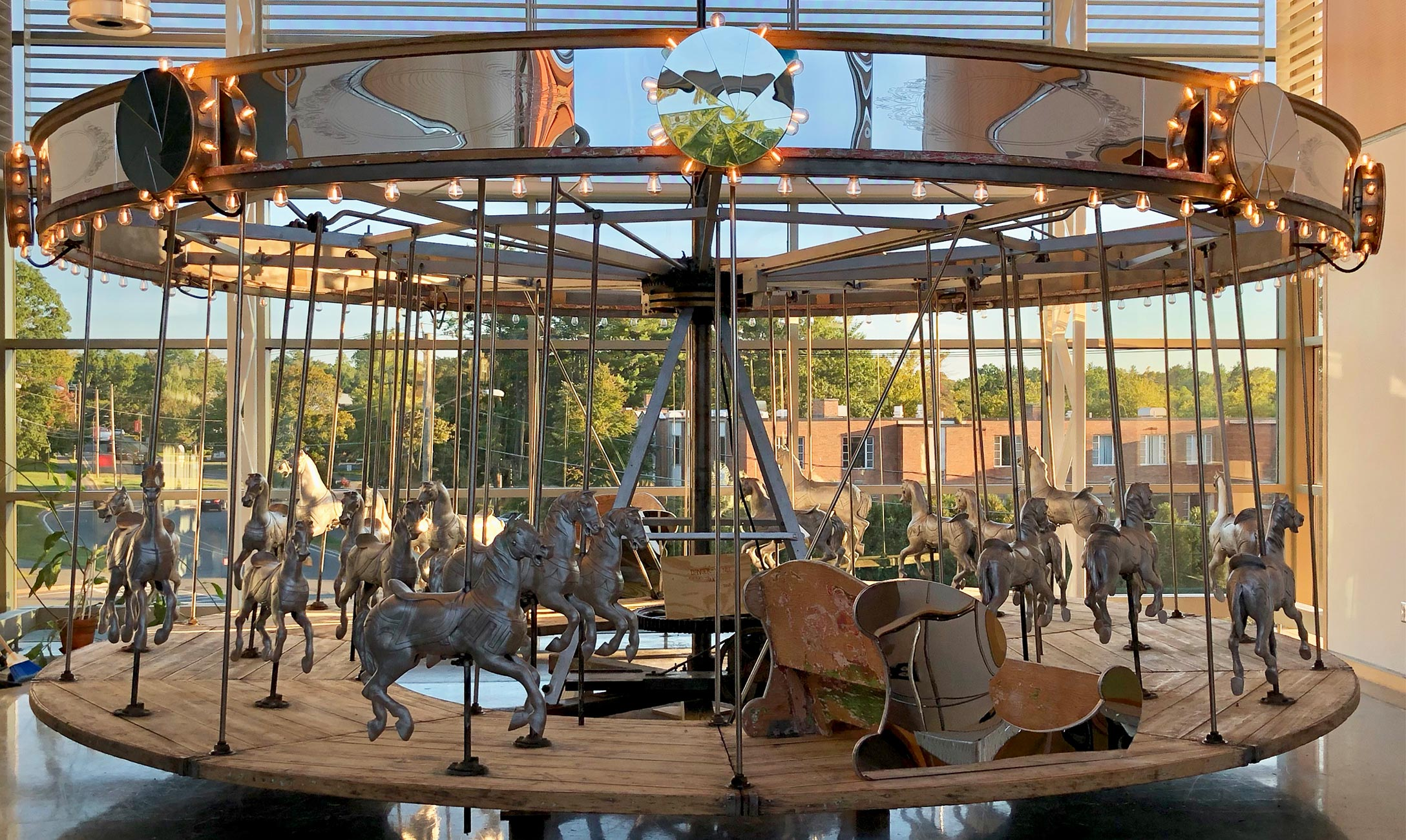 Refurbished carousel in front of large windows.