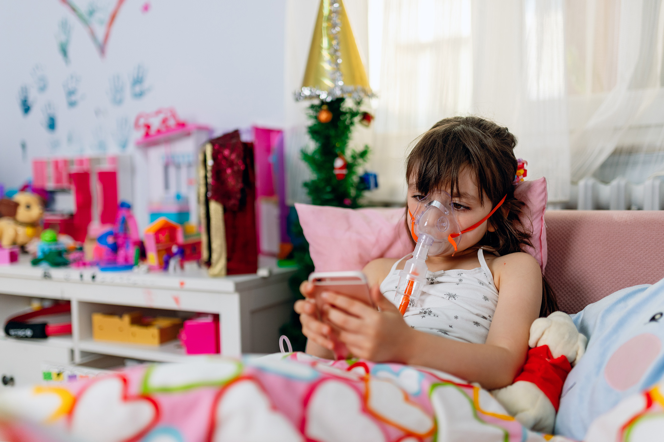 Girl with oxygen mask in bed playing with phone.