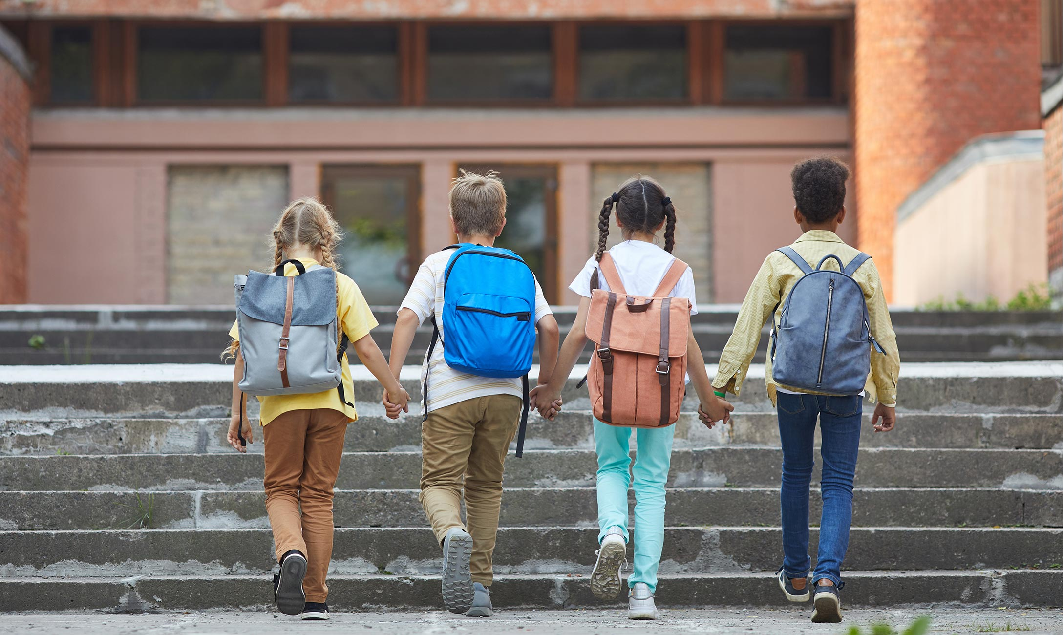 Four children with backpacks walking up steps holding hands.