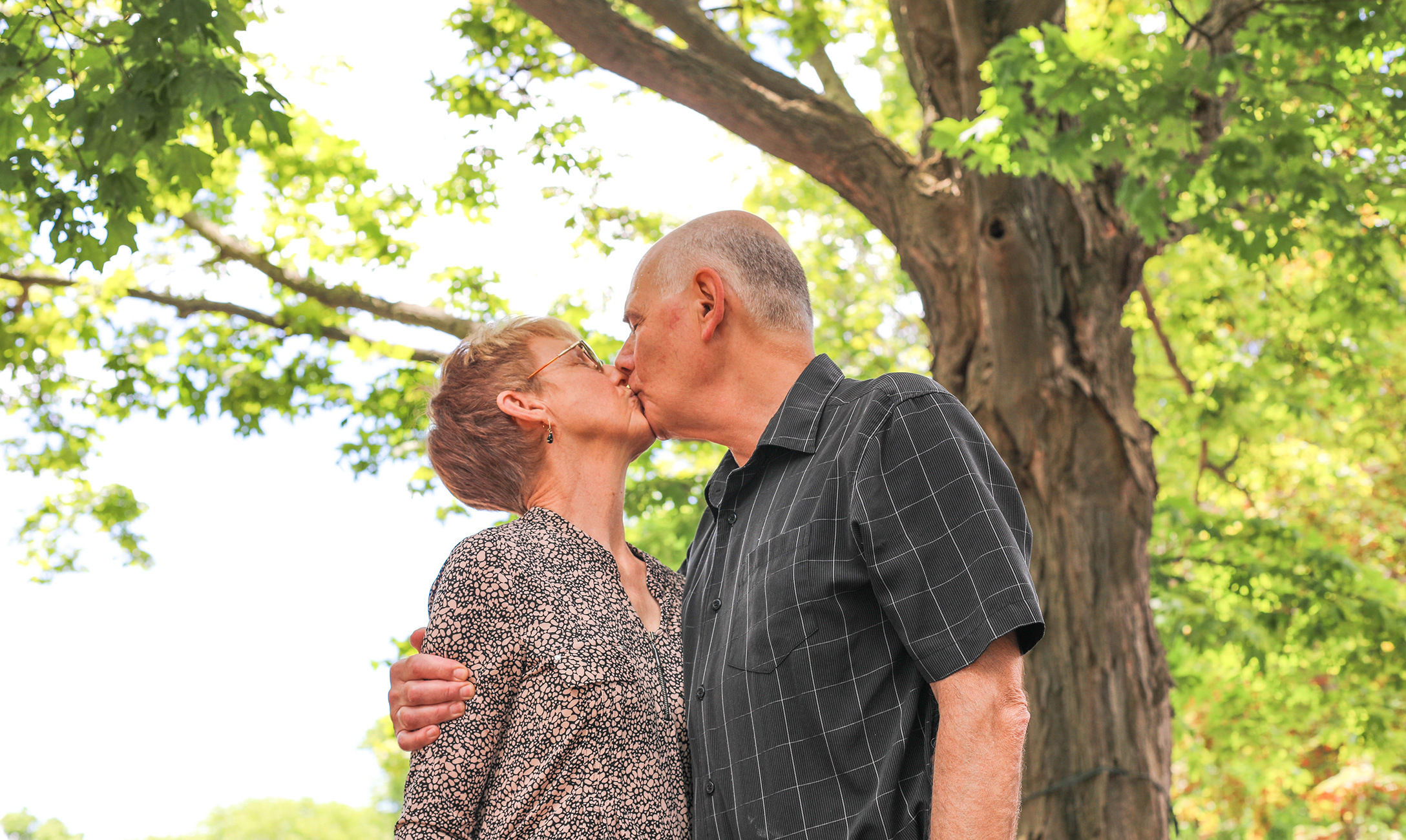 Two people kissing under a tree.