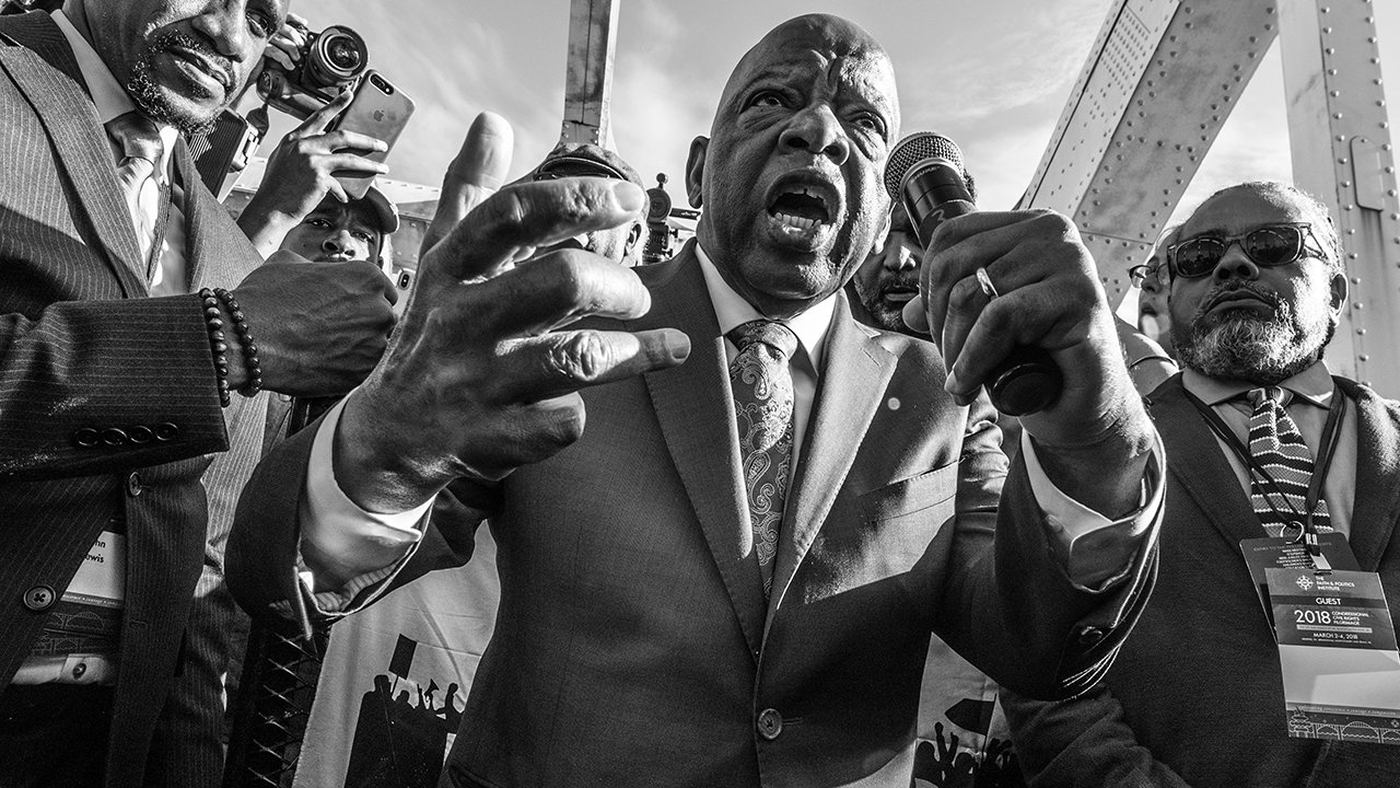 Black and white photograph looks up at crowd with Rep. John Lewis at center holding microphone.