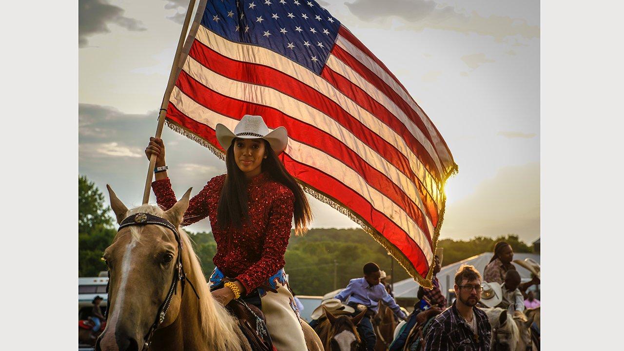 Rodeo rider on horseback brandishing a huge U.S. flag