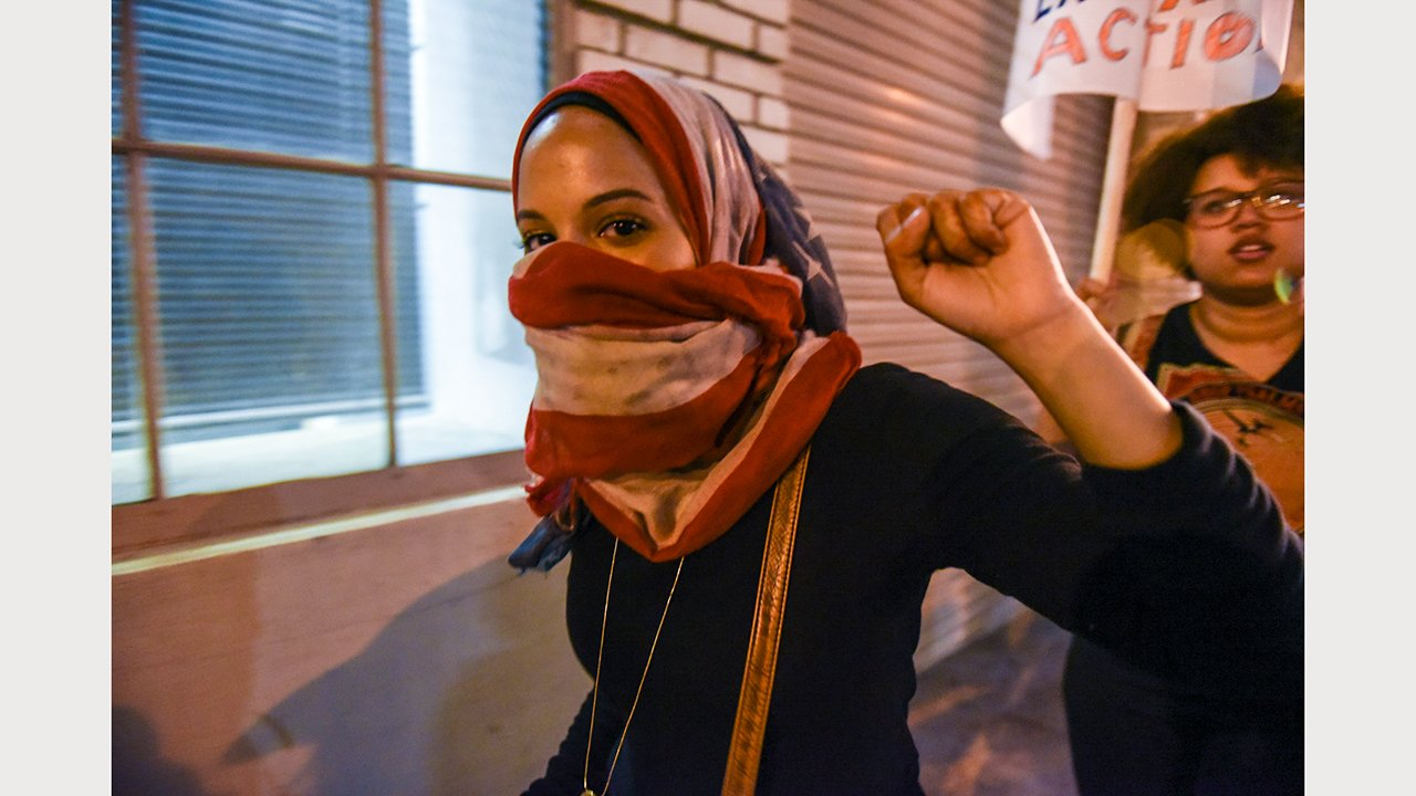 A young protestor wearing a headscarf raises her fist