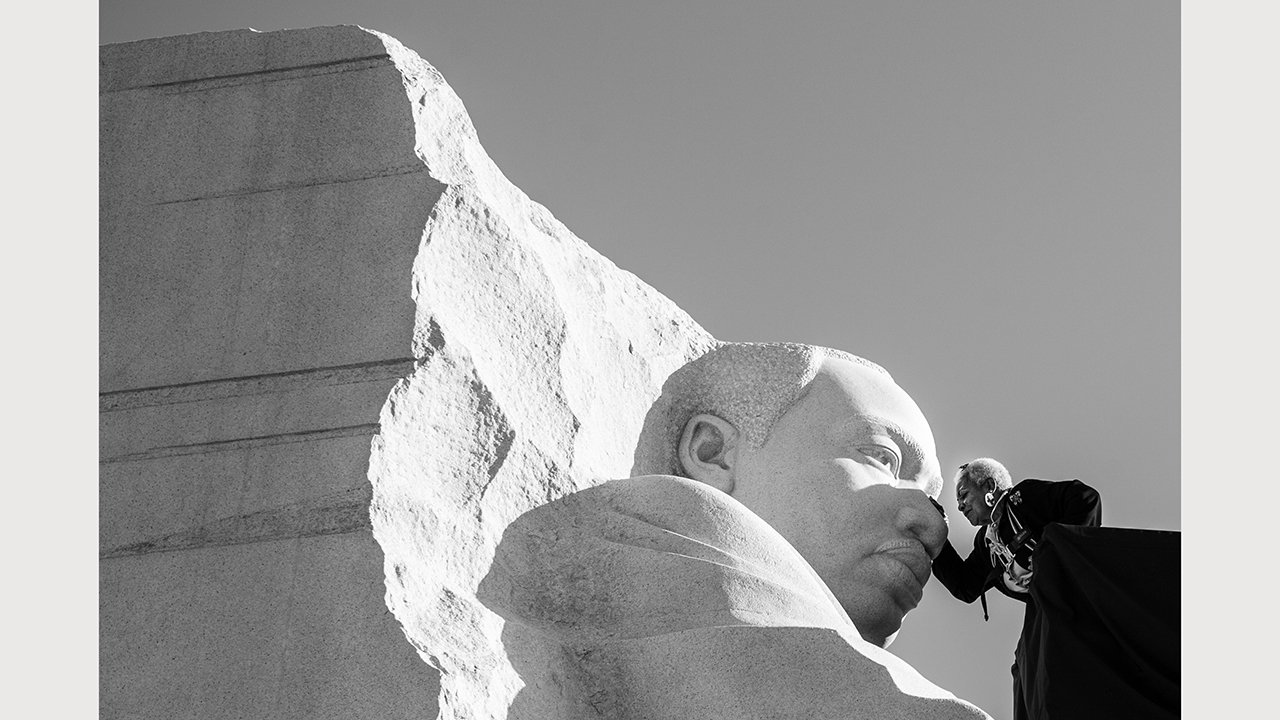 A person is shown fondly touching the face of the memorial statue of Dr. Martin Luther King Jr. In Washington, D.C.
