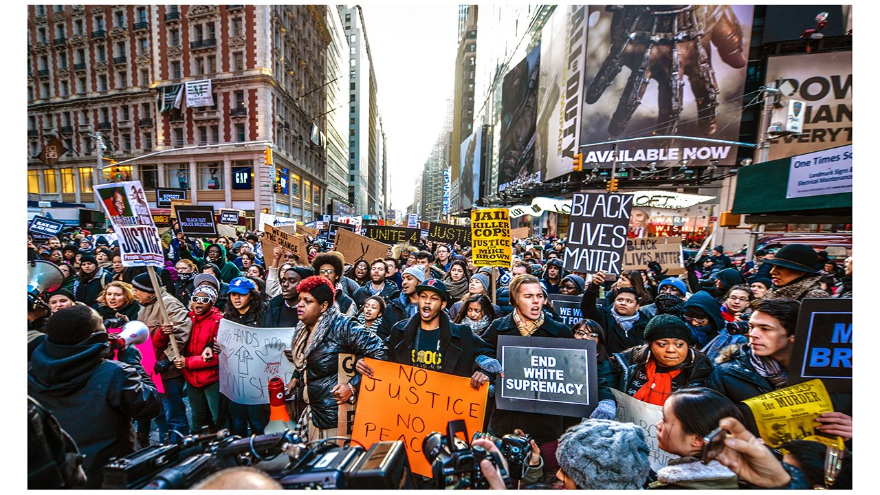 Group of protestors holding signs, gathered in a New York City street.