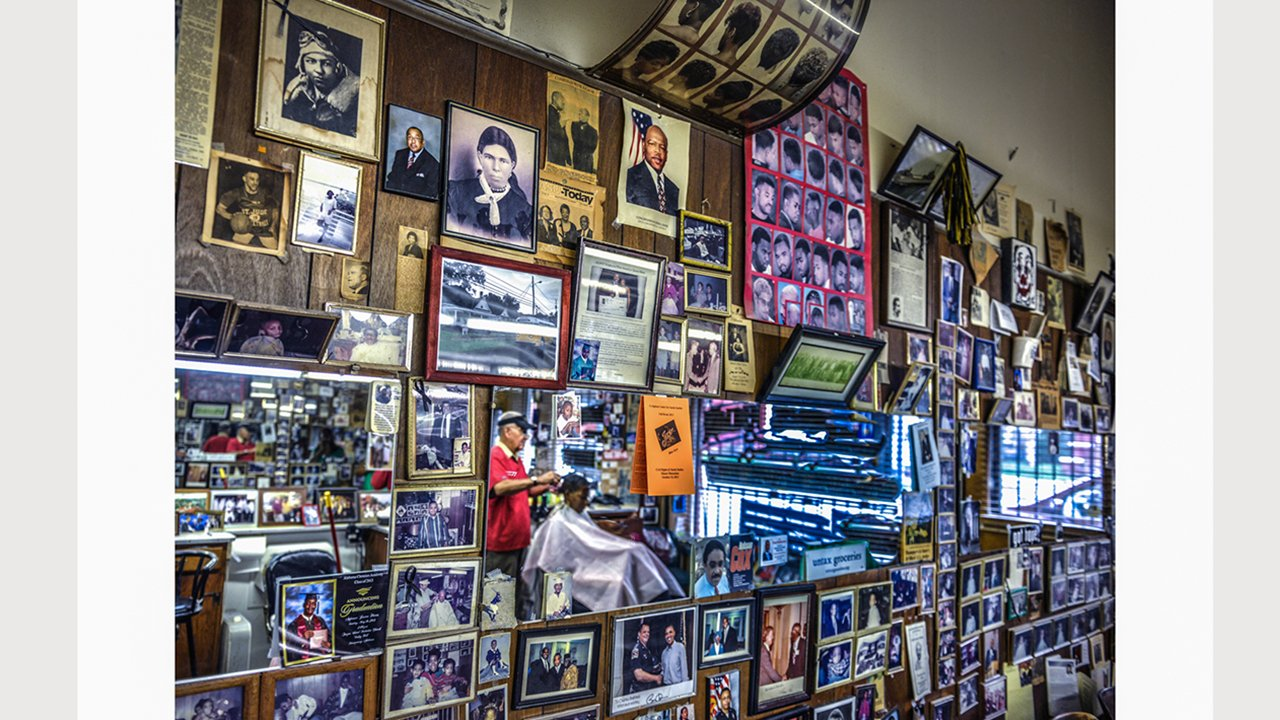 A wall of photographs and mementos is shown along with mirrors reflecting the activities underway in the barber shop.