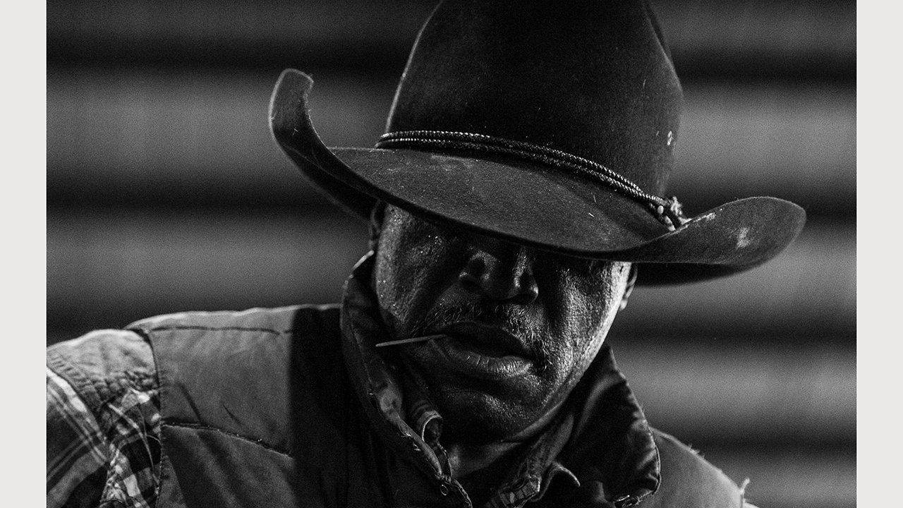 Close up black and white portrait shows only the lower half of a face, with the upper half obscured by a dark cowboy hat.