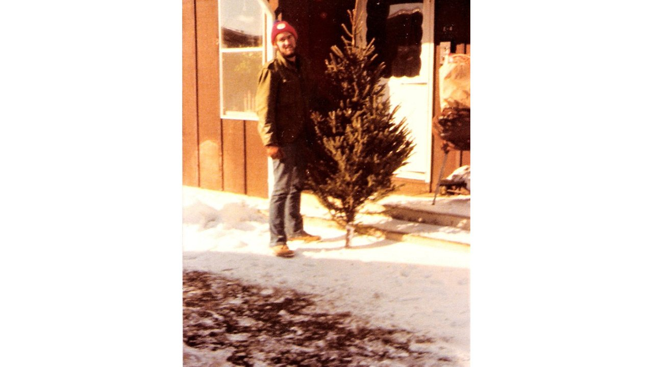 Bearded person in knitted cap holds Christmas tree in front of a North Apartments building.