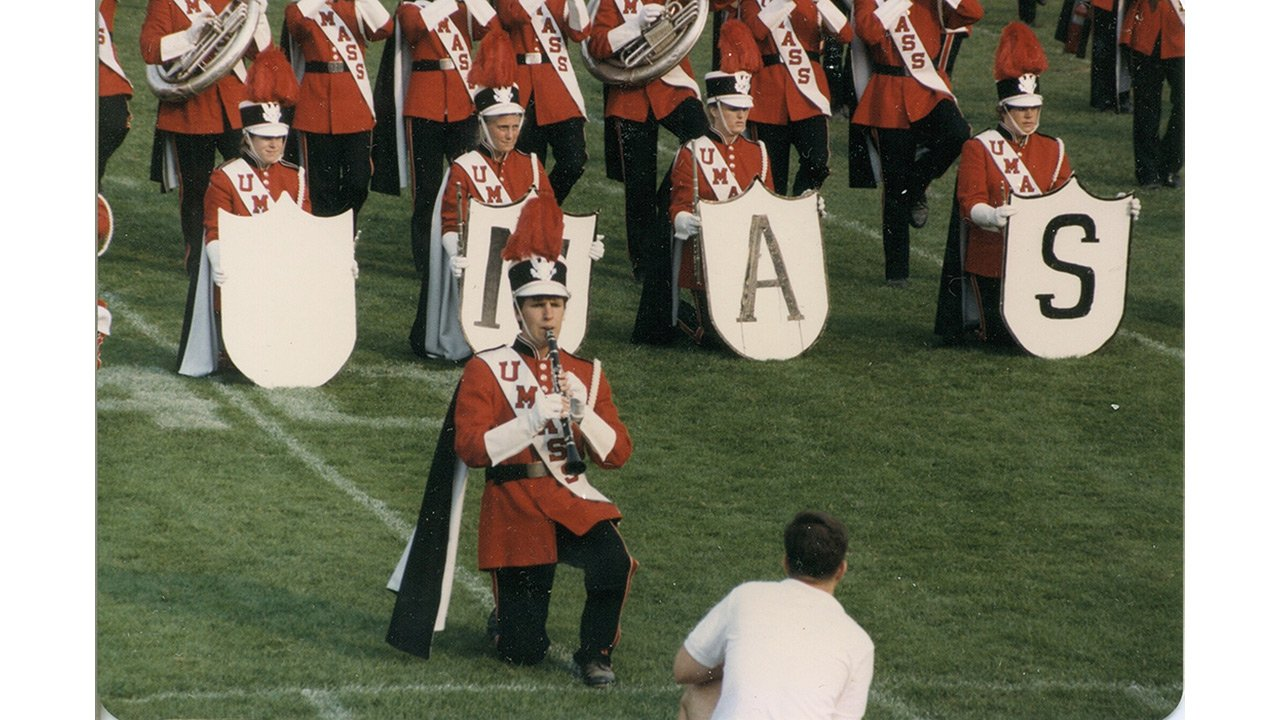 Member of the UMass marching band kneeling while playing on a field.