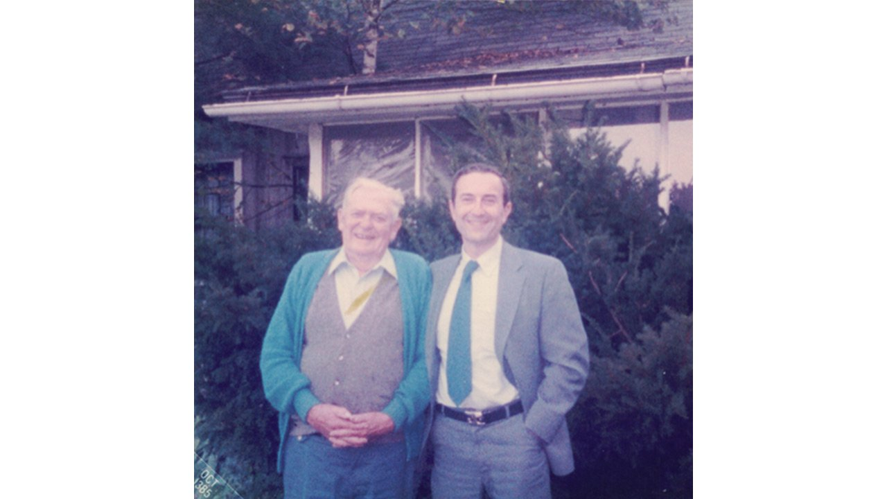 Two people posing in front of evergreen trees.