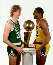 Larry Bird and Magic Johnson pose next to the NBA Championship trophy.