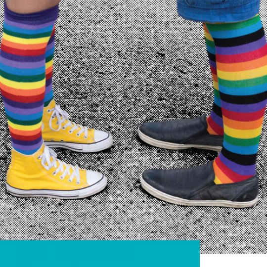 Two pairs of legs with colorful socks facing each other.