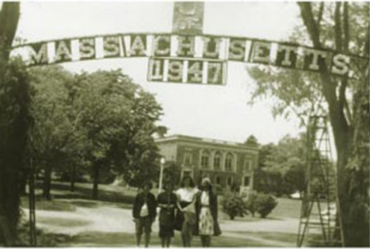Four students standing under sign that reads Massachusetts 1947.