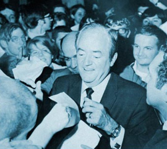 Humbert Humphrey signing autographs in a crowd of people.