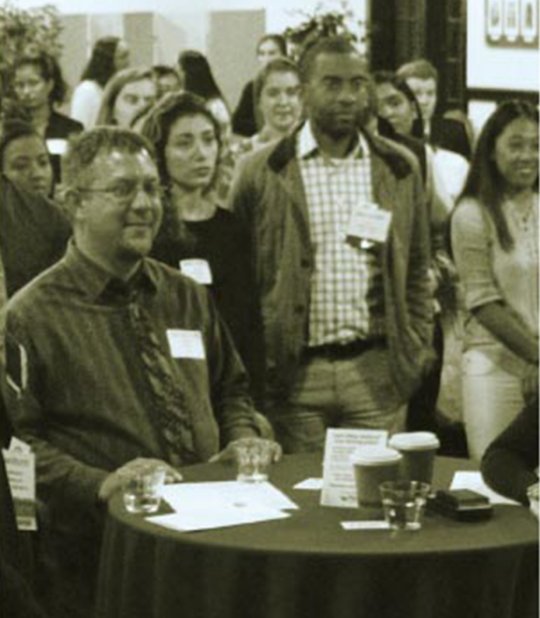 Crowd standing behind a round table at an event.