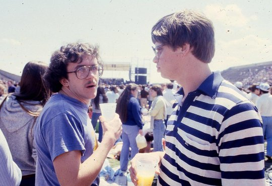Two friends standing in a crowd in the 1970s