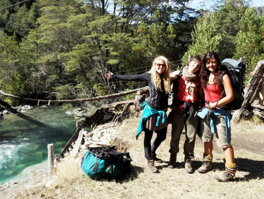 Three backpackers posing next to a river in Patagonia.