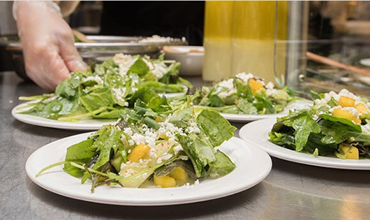 Plated salads on a cafeteria serving table
