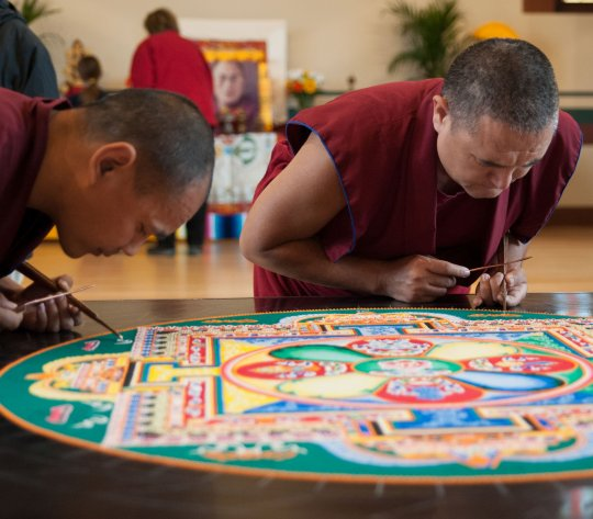 Two Tibetan monks create a sand mandala inside Old Chapel