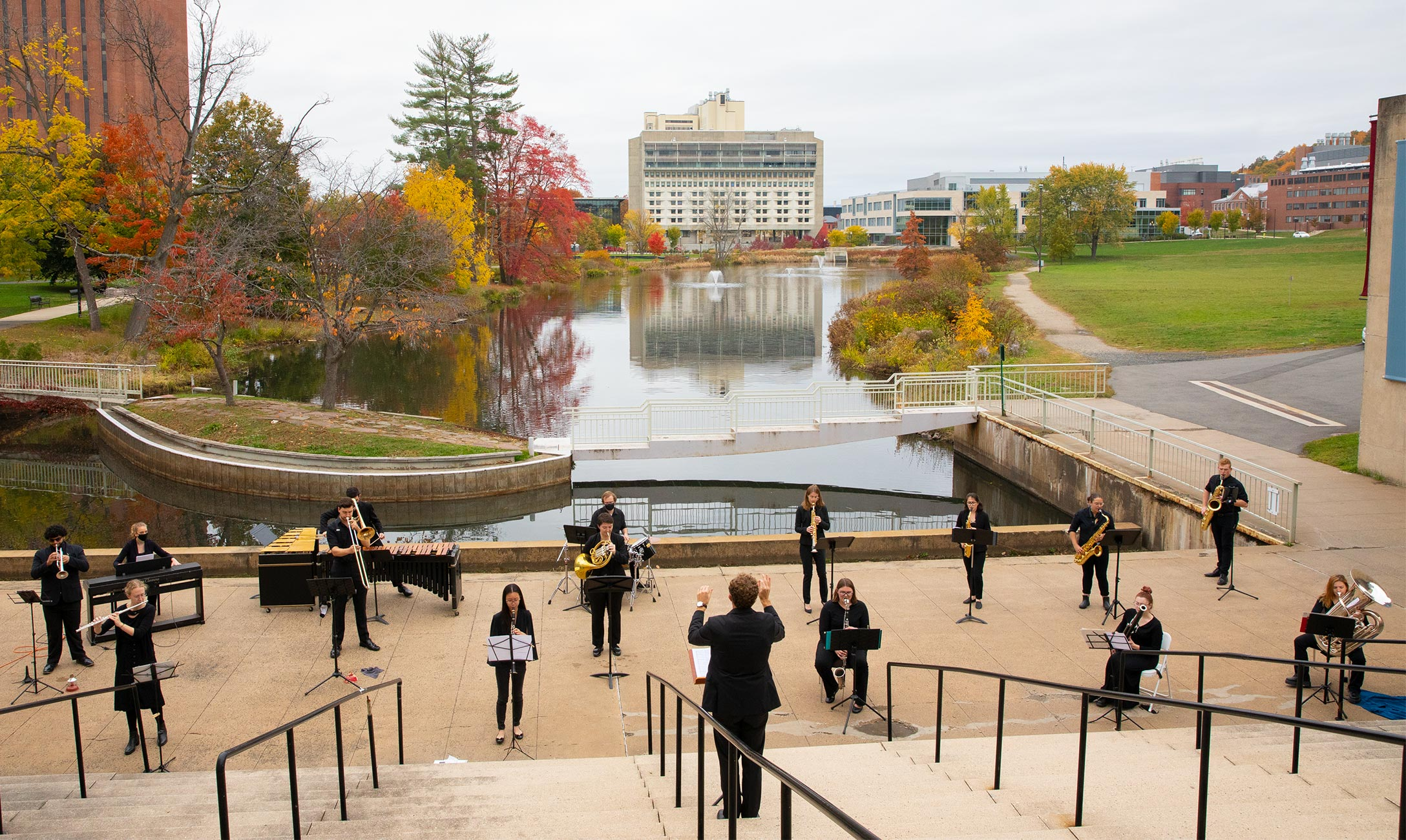 UMass wind ensemble playing on steps of the Fine Arts Center. The campus pond, fall foliage, and other buildings are seen in the background.