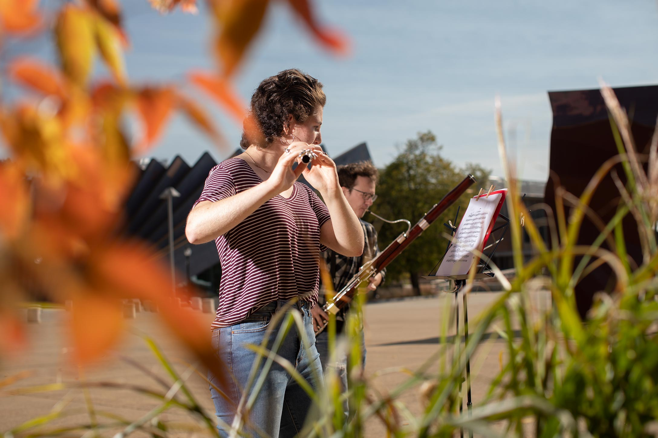 A Wind Ensemble member practices on campus outdoors.