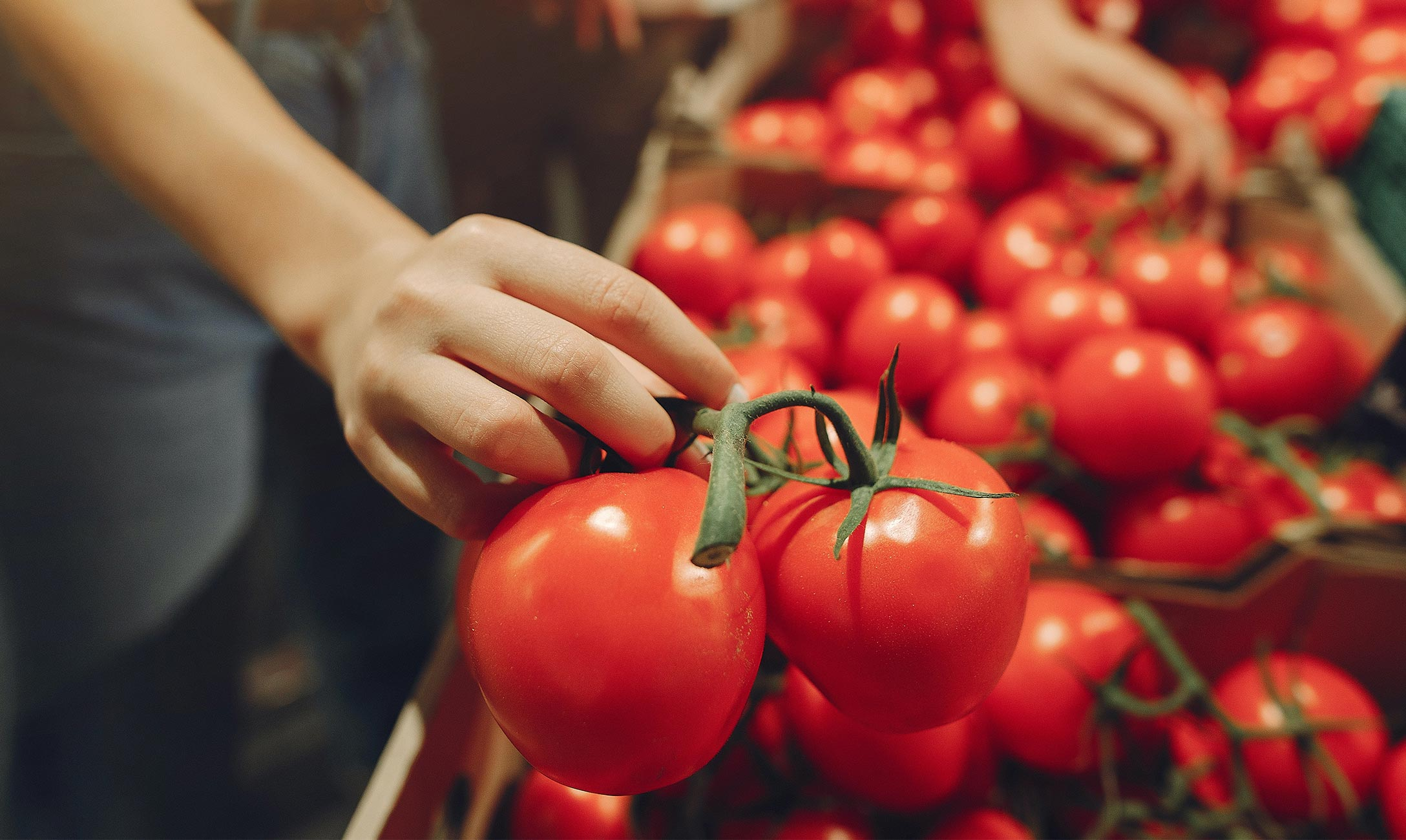 Hand grabbing tomatoes in a market.