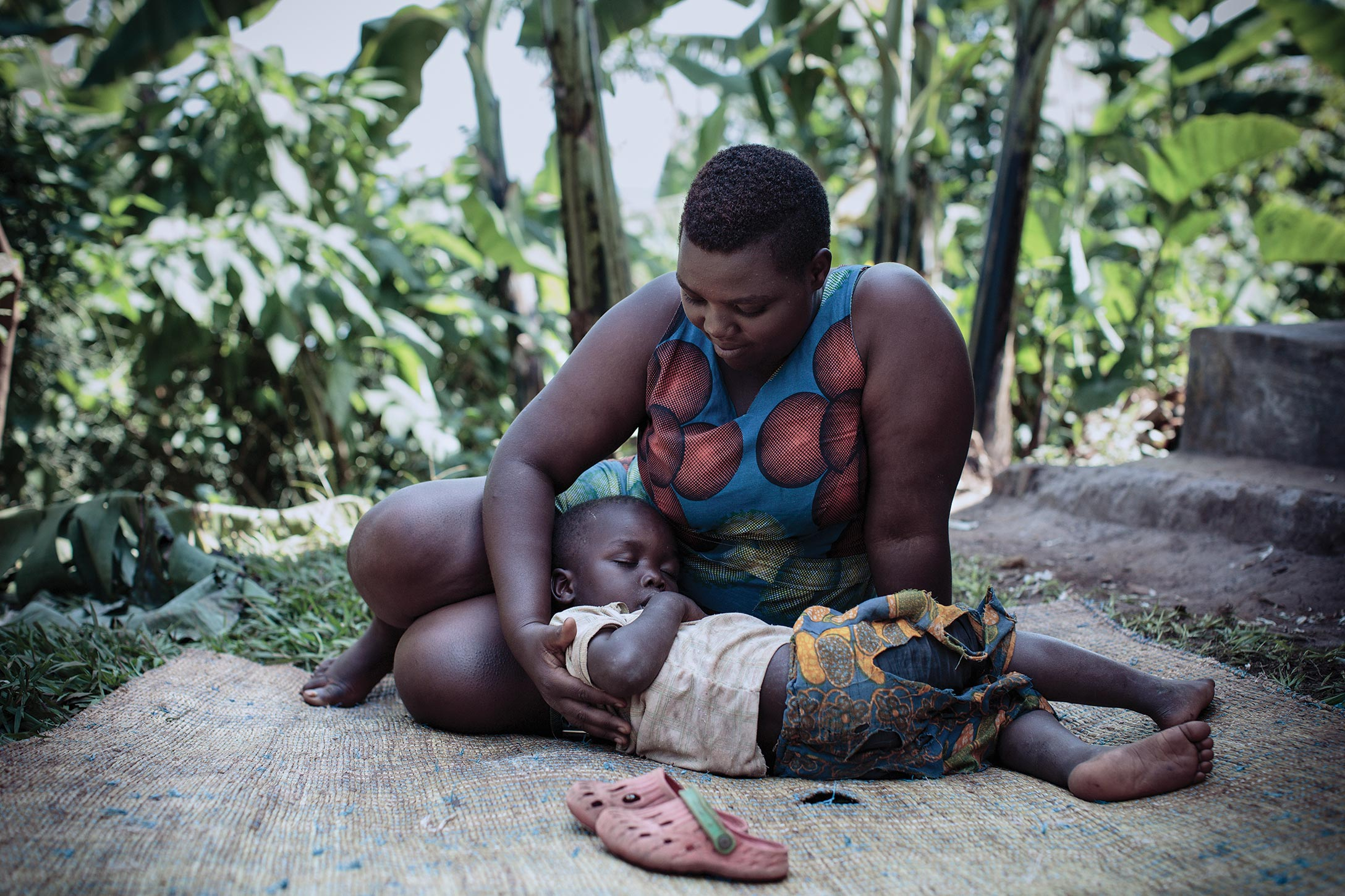 A toddler reclines as his mother cradles his head in her lap and gazes down at her son.