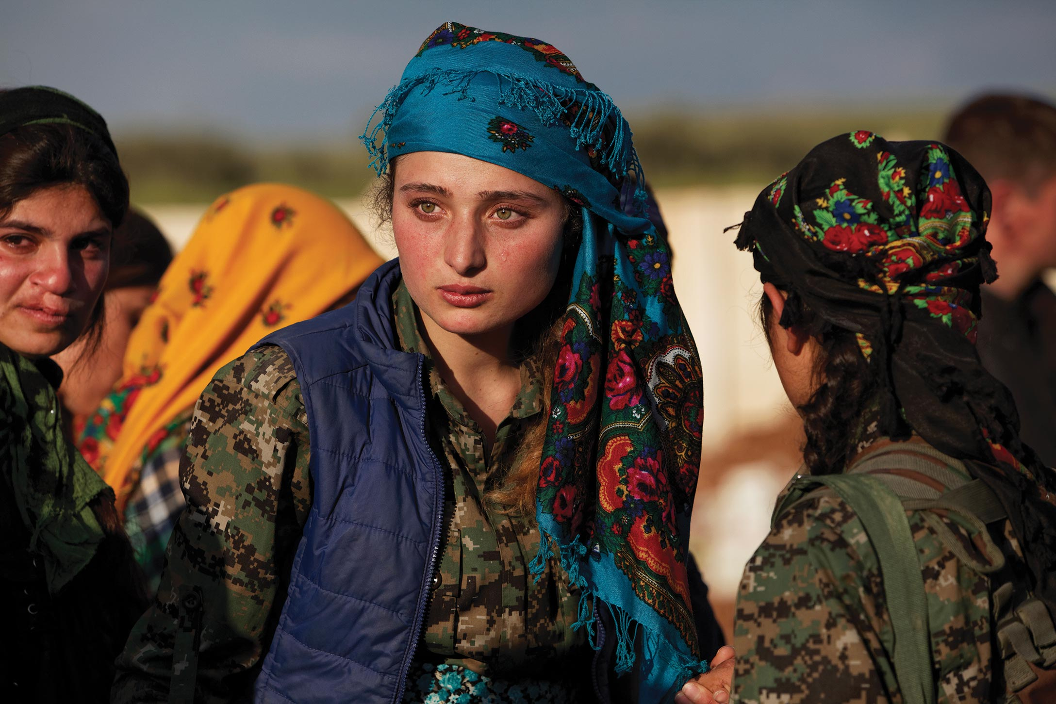 A Kurdish YPJ fighter looks over the wreckage left by fighting on a street.