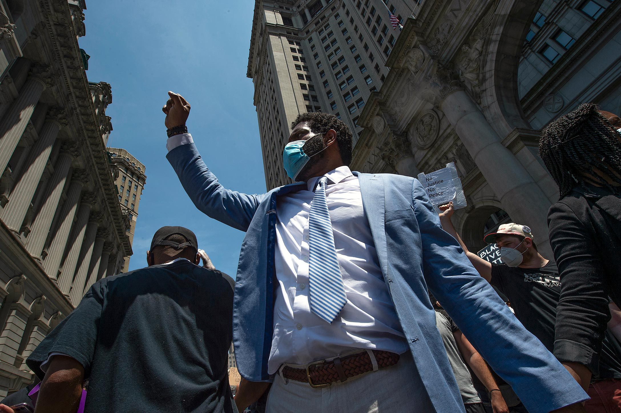 Looking upward we see a man wearing a suit and a face mask taking part in a demonstration. He raises his fist high in the air. Other demonstrators can be seen holding signs.