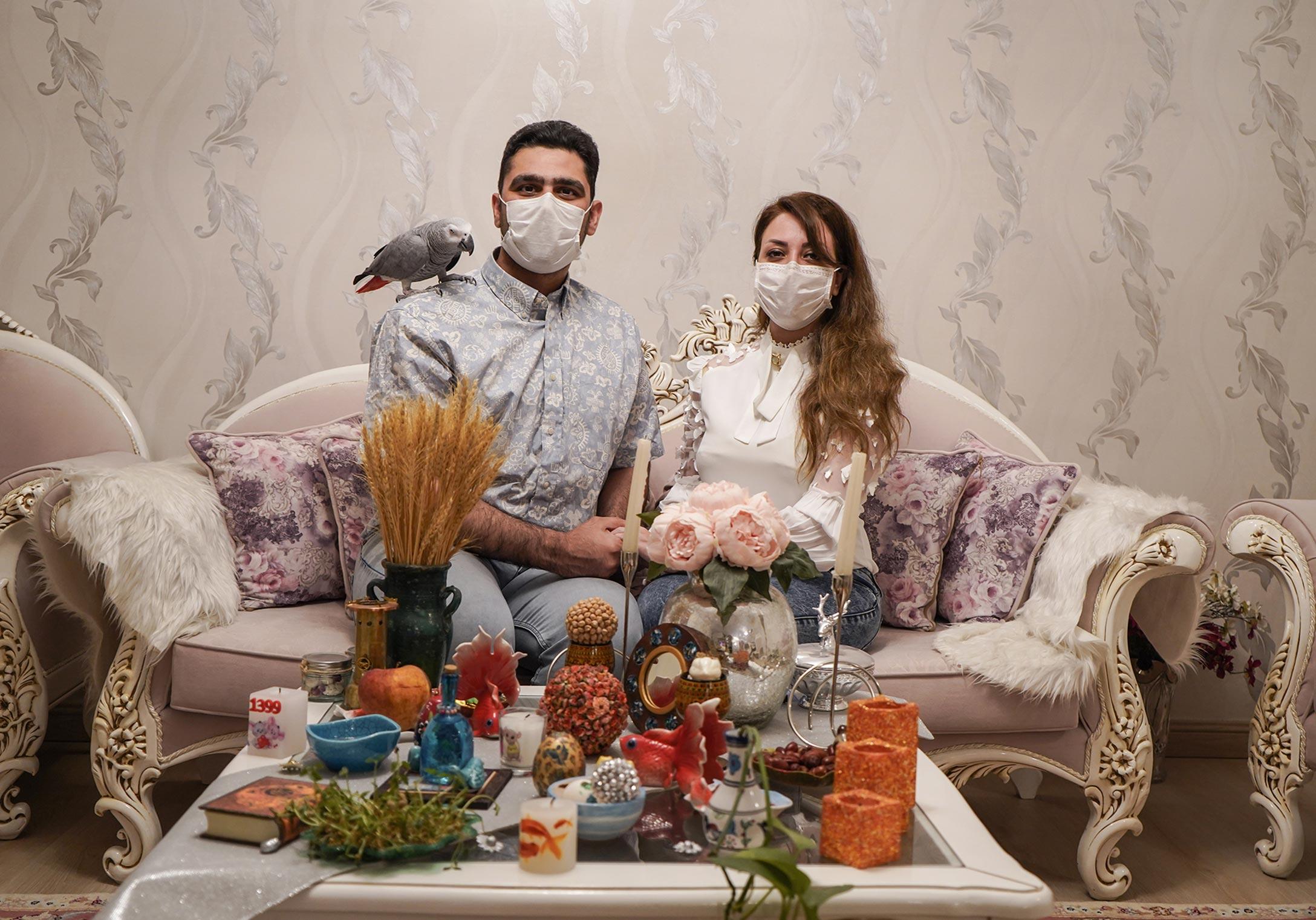A couple wearing face masks are shown on a sofa surrounded by food and pets.